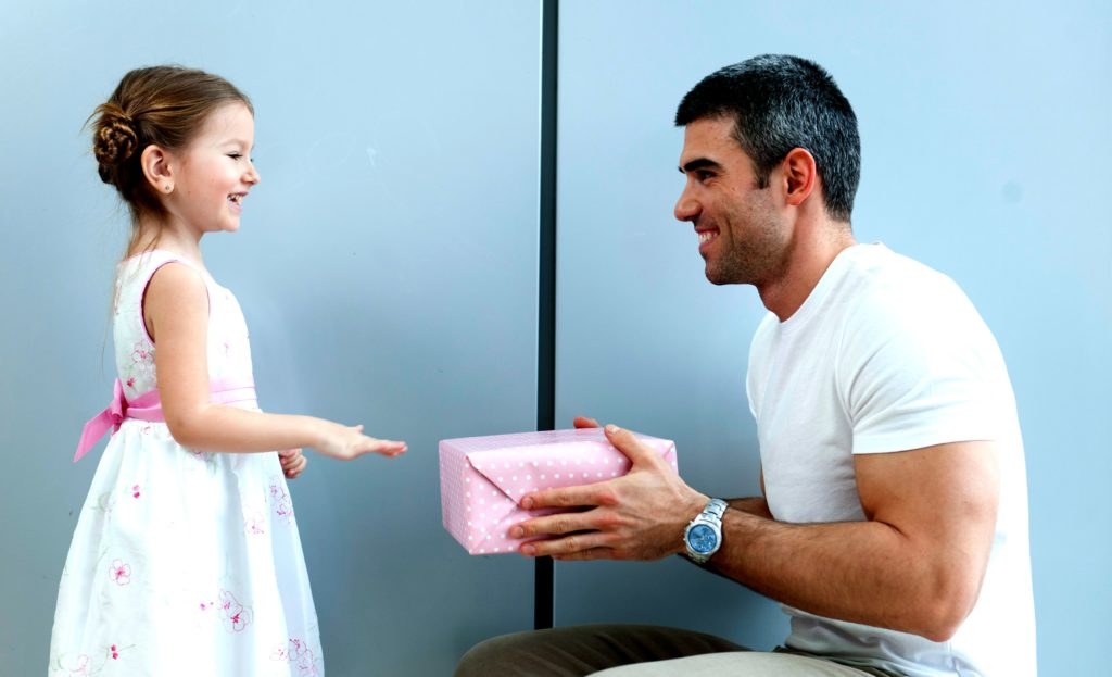 Father and daughter exchange a gift.