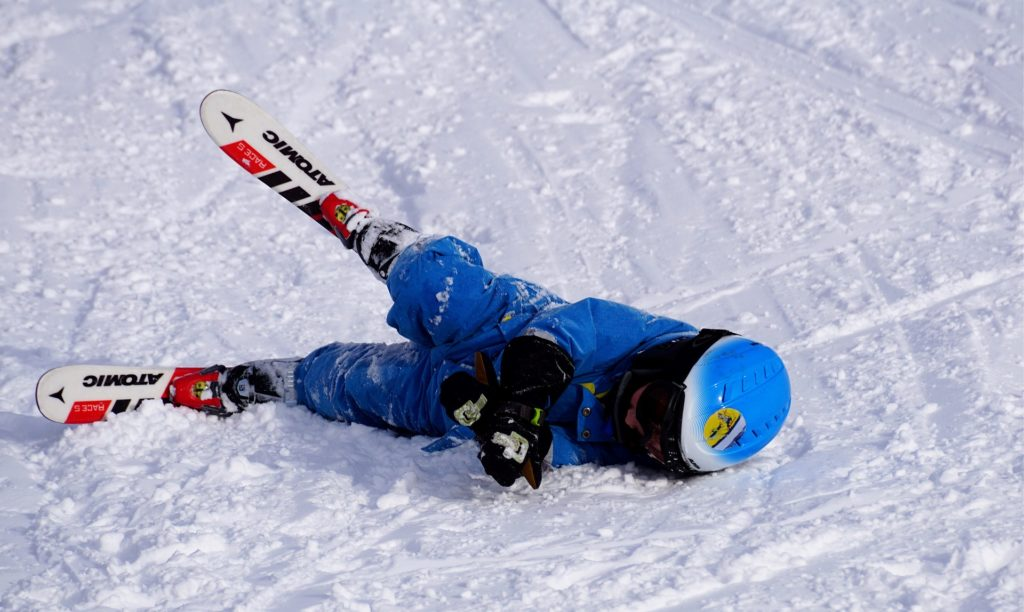 Child on skis falls on the snow.