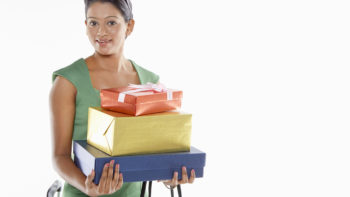 Woman carrying a stack of gift boxes.