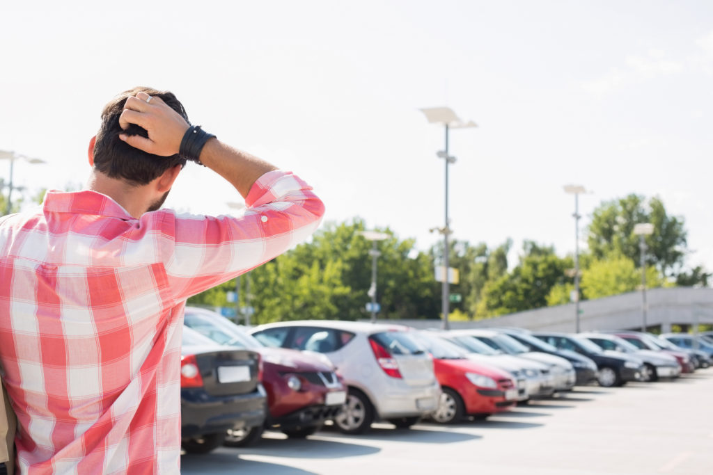 man in parking lot looking for car