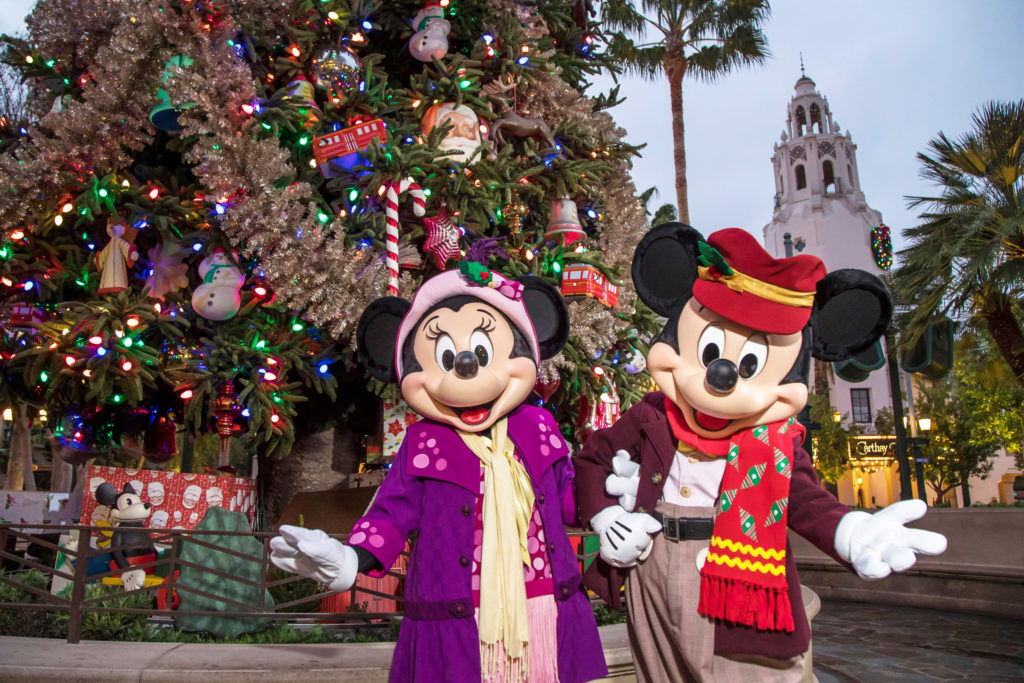 Minnie Mouse and Mickey celebrating Christmas in Disneyland in front of a decorated tree.