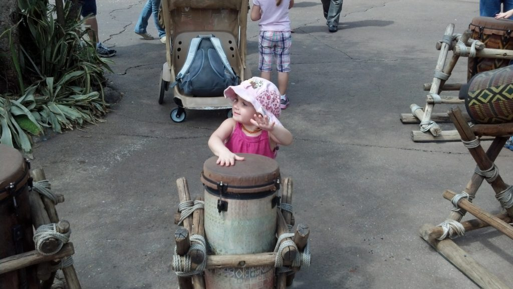 toddler wearing cheetah print hat banging on drum at animal kingdom disney world