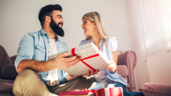 bearded man receiving present from woman- TravelingMan