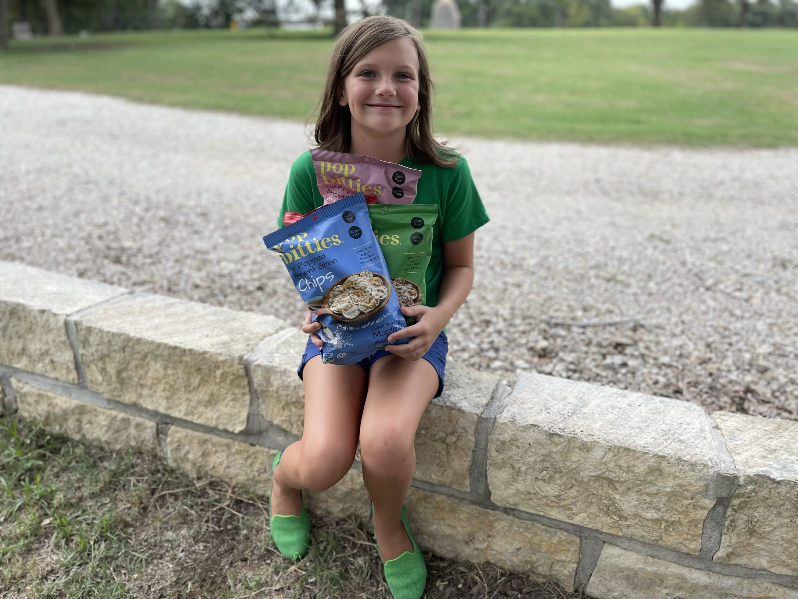 girl sitting on stone wall holding bags of pop bitties snacks