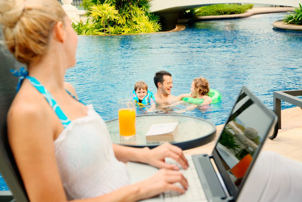 Woman using a laptop next to a pool.