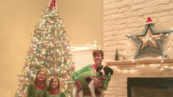 kids and dog with matching christmas pajamas in front of christmas tree