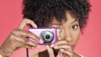 black woman taking a picture with a pink point and shoot camera, background is coral