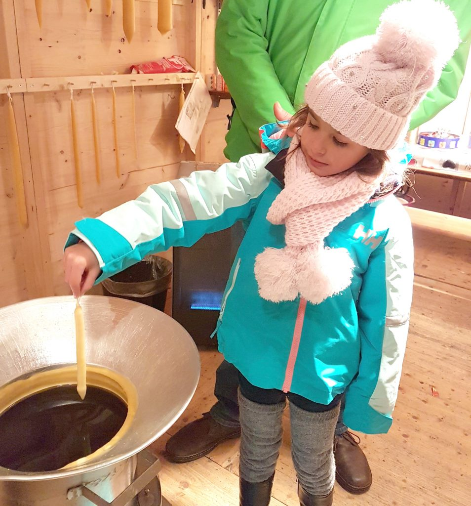 A child making a candle at a European Christmas market.