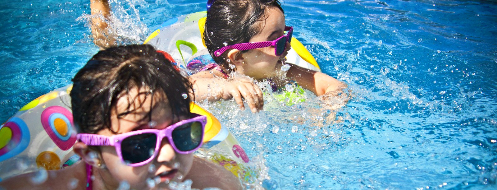 Girls using floats and sunglasses in a swimming pool