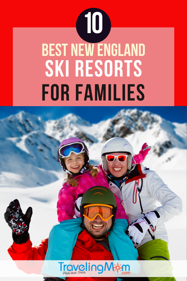 Father and two kids smiling and waving in ski gear in front of snowy mountain
