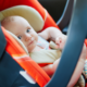 baby girl in orange infant car seat