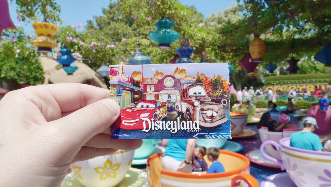 Disneyland ticket in front of the tea cups