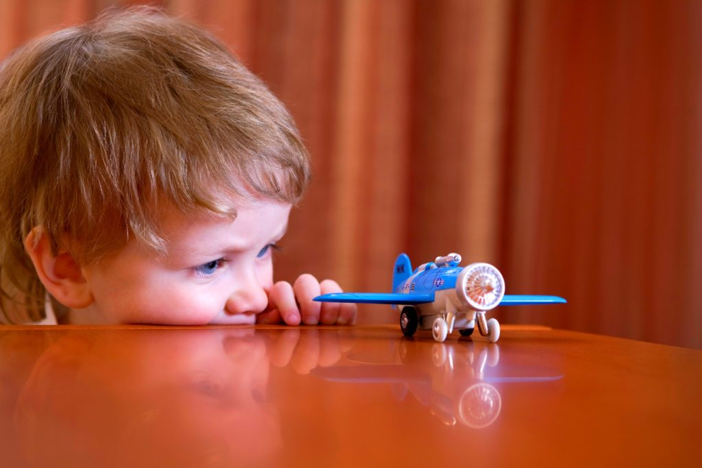 Little boy playing with a toy airplane.