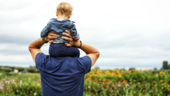 baby on dad's shoulders looking over green grass and ocean