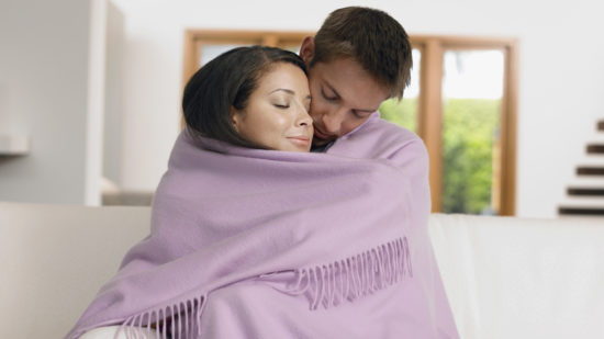 Couple snuggling in blanket on a romantic getaway.