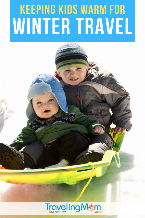 two young boys sledding down a snowy hill