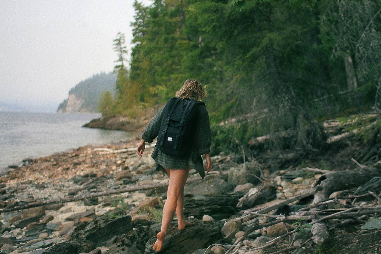 stay fit on vacation like this woman walking along rocky coast