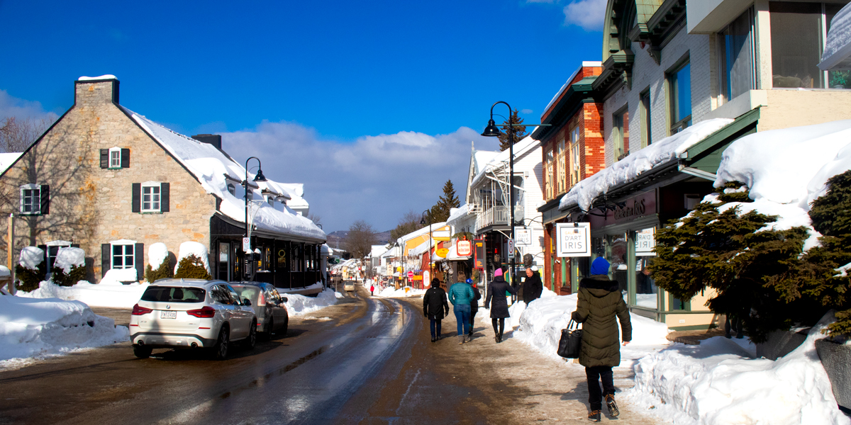 photo, a group of people walk down the main street in Baie-Saint-Paul, Quebec in the Charlevoix region.