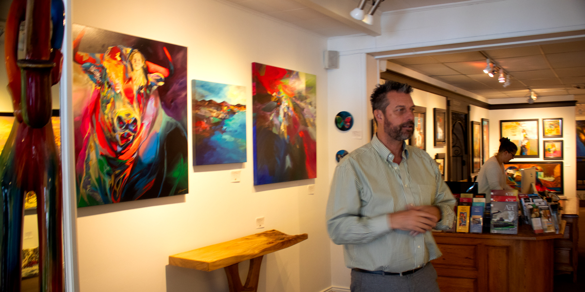 photo, gallery owner in talking while standing in front of three brightly colored paintings