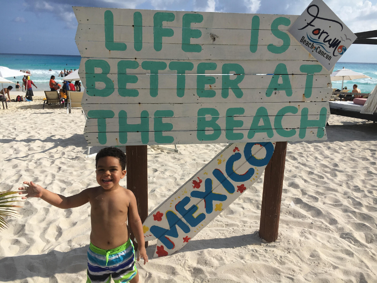 "Young boy at the beach standing in front of ""Life is Better at the Beach"" sign."