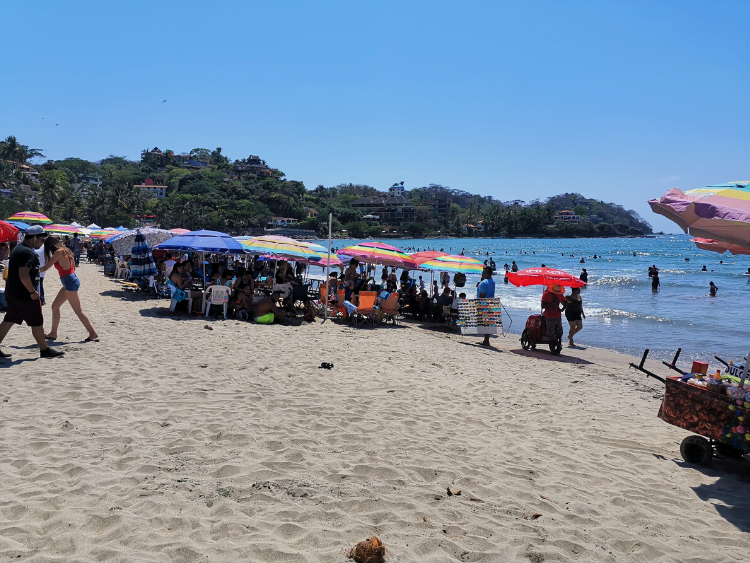 Sayulita Beach, packed with visitors who set up chairs and beach umbrellas.