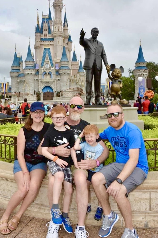 family in front of Disney castle - travelingmom