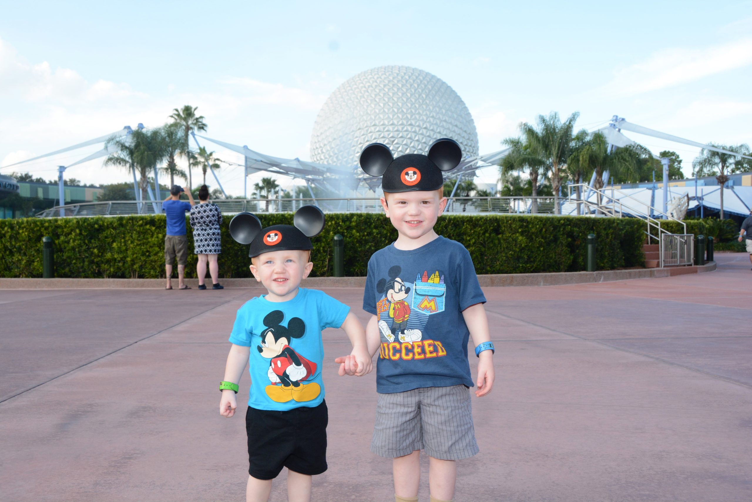 two young boys wearing mouse ears in Epcot - travelingmom