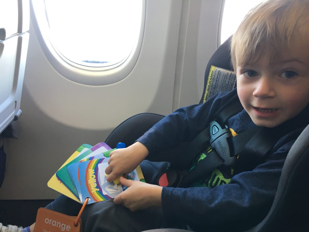 toddler playing with water wow set on plane