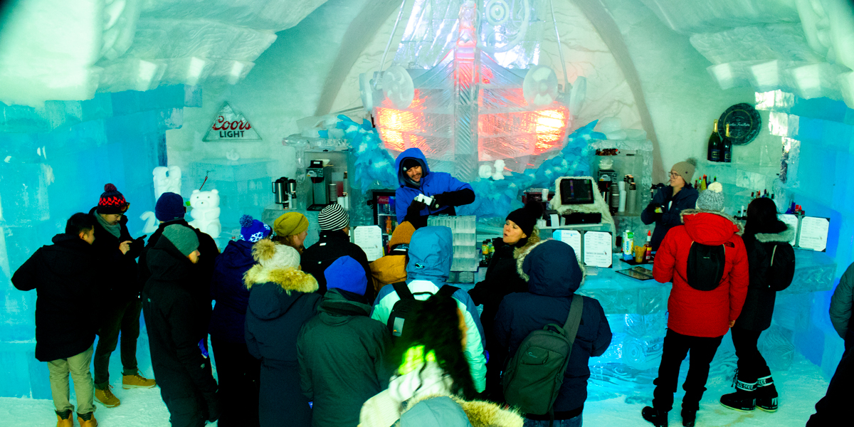 photo, people standing around a bar made of ice while a bartender is making drinks