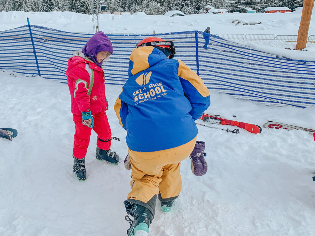 Kids learning how to put on skis at ski school.