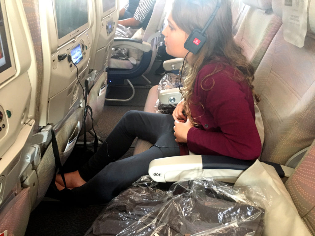 preteen on long flight in airline seat watching seat back entertainment with headphones and foot hammock