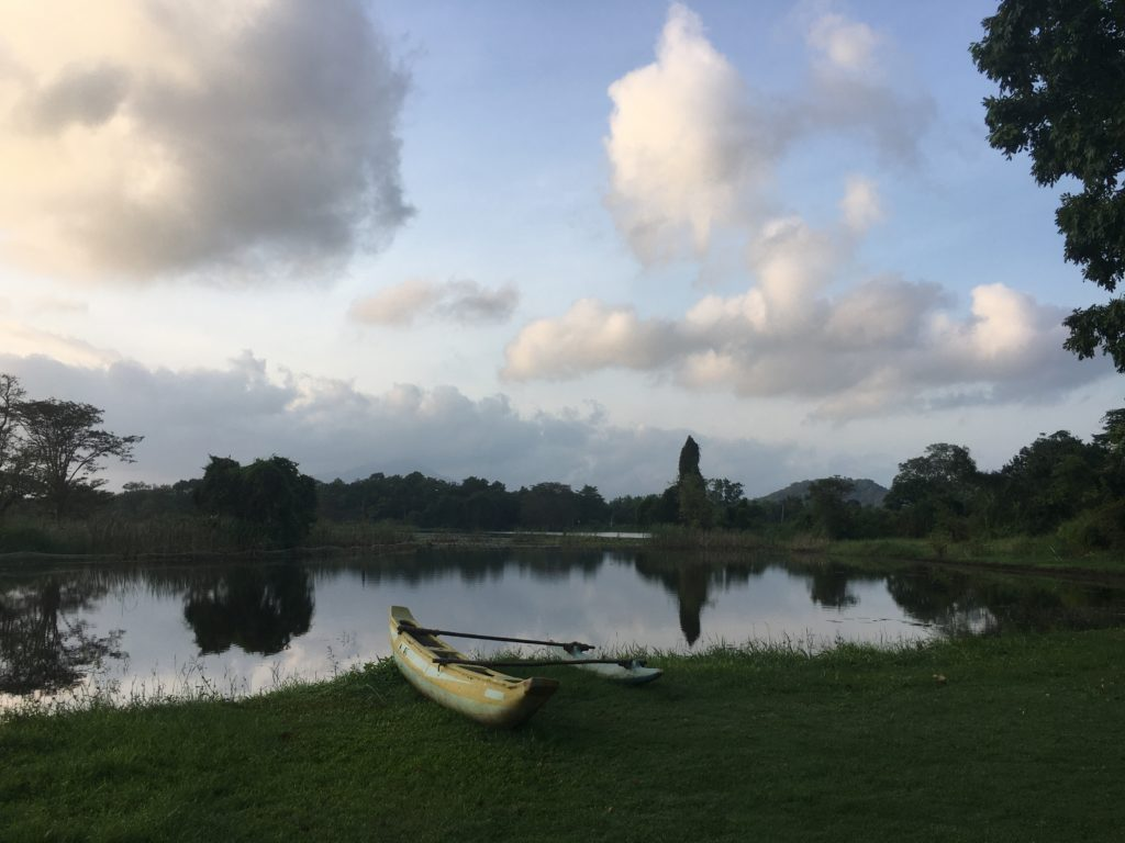boat near lake in Sri Lanka at sunrise with blue sky and puffy clouds
