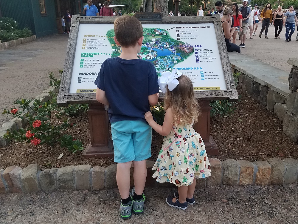 Kids looking at map at Disney World Animal Kingdom on a vacation made easier with a travel checklist