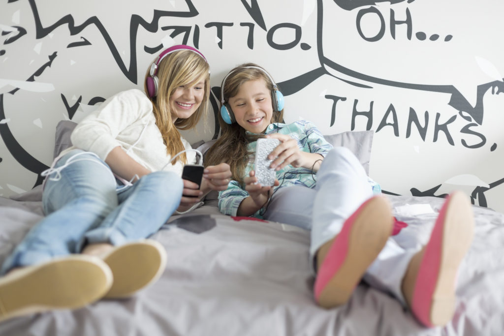 teens listening to audiobooks on bed