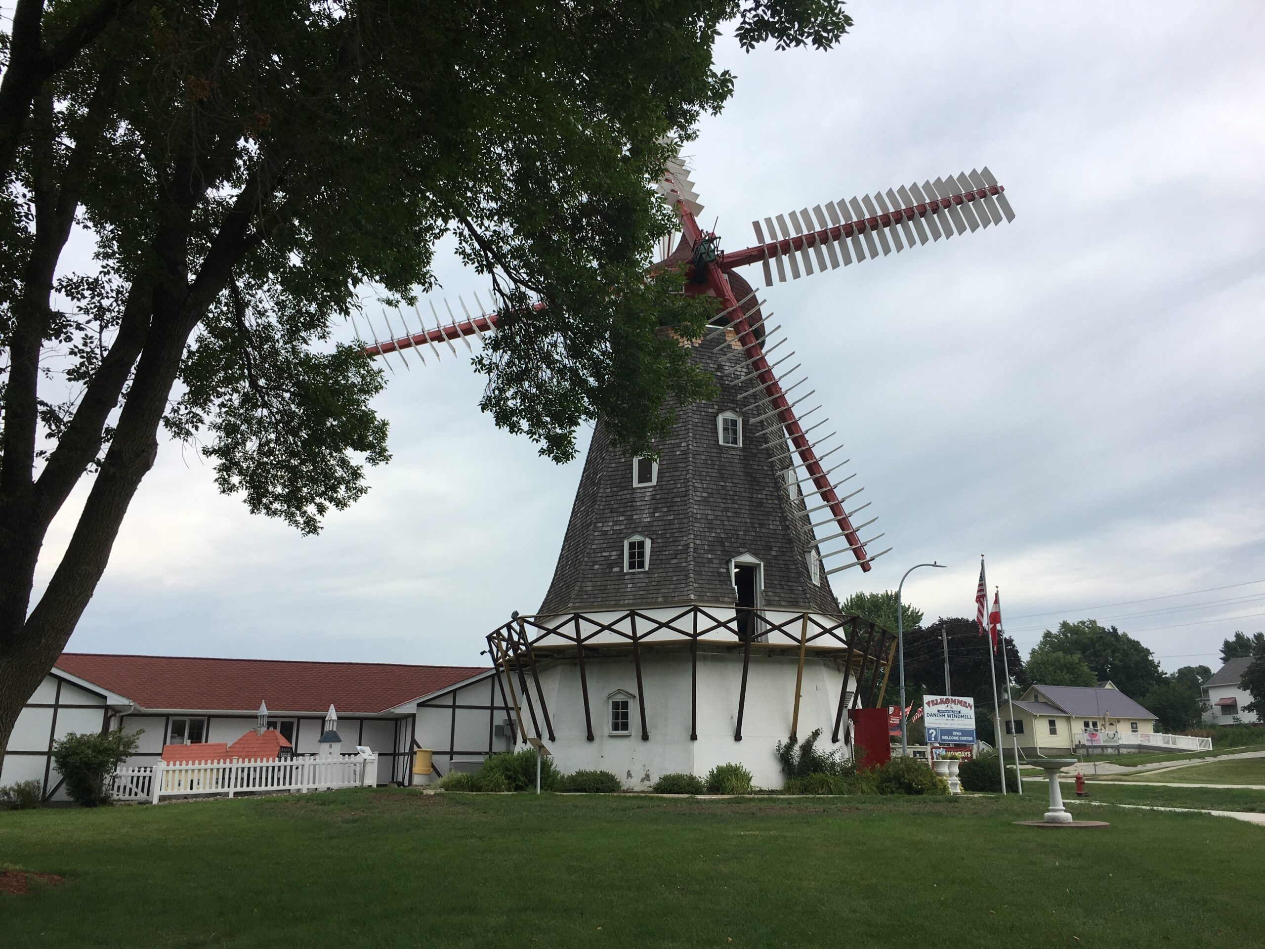 large windmill with trees and green grass