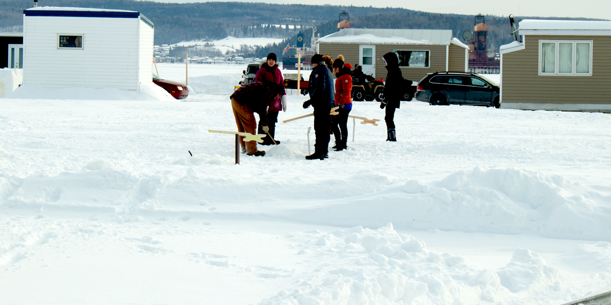 photo, seven people setting up ice fishing lines