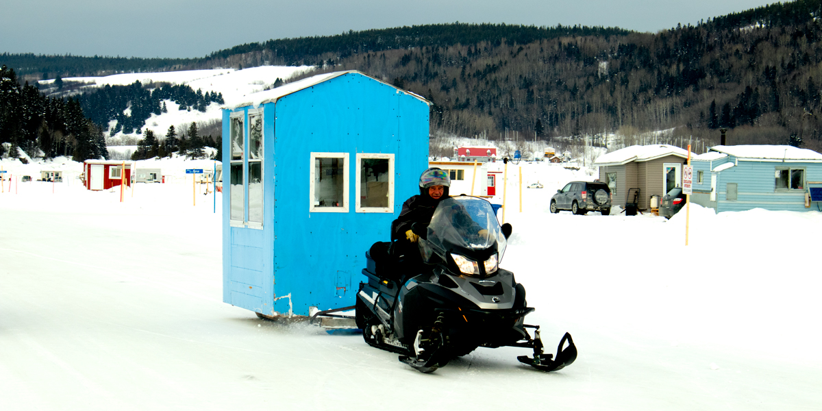 photo, fishing shack being pulled by a snowmobile