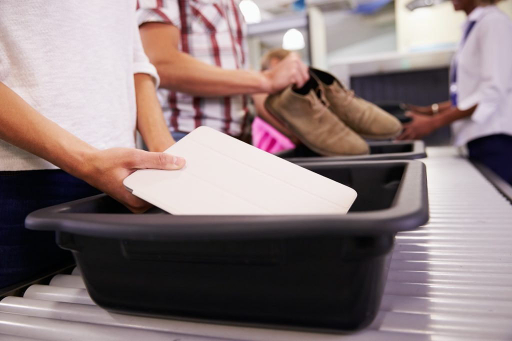 a laptop is placed into a bin at the security checkpoint at the airport to go through the scanner.
