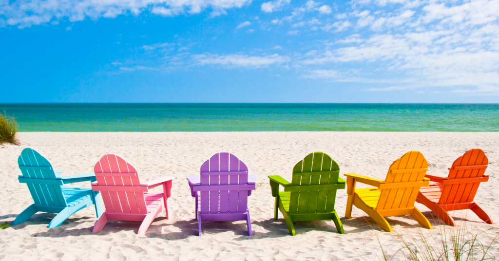 Chairs in a row on the beach for beach vacation packing list post