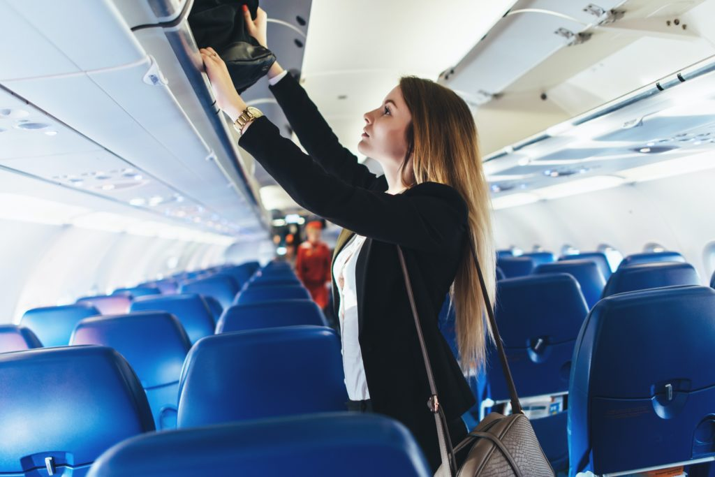 A young caucasian woman is loading her carry-on luggage into the overhead bin on an airplane. She's dressed in business attire and has long brown hair.