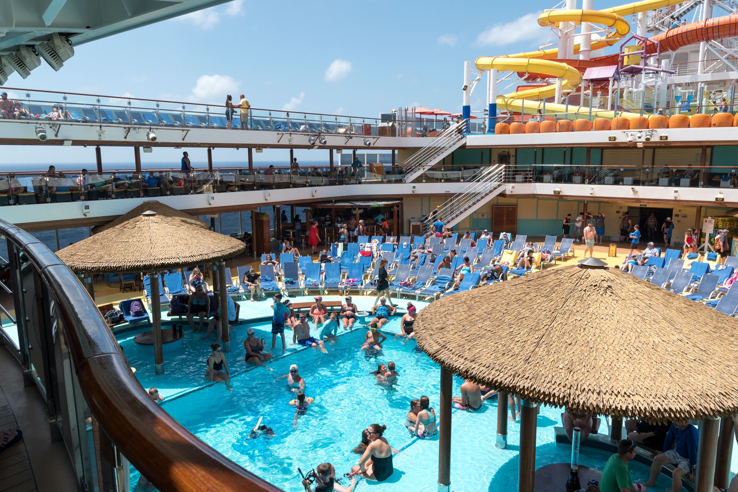 A busy pool deck on a cruise ship with dozens of people in swimsuits. There are two twisting slides on the upper deck.