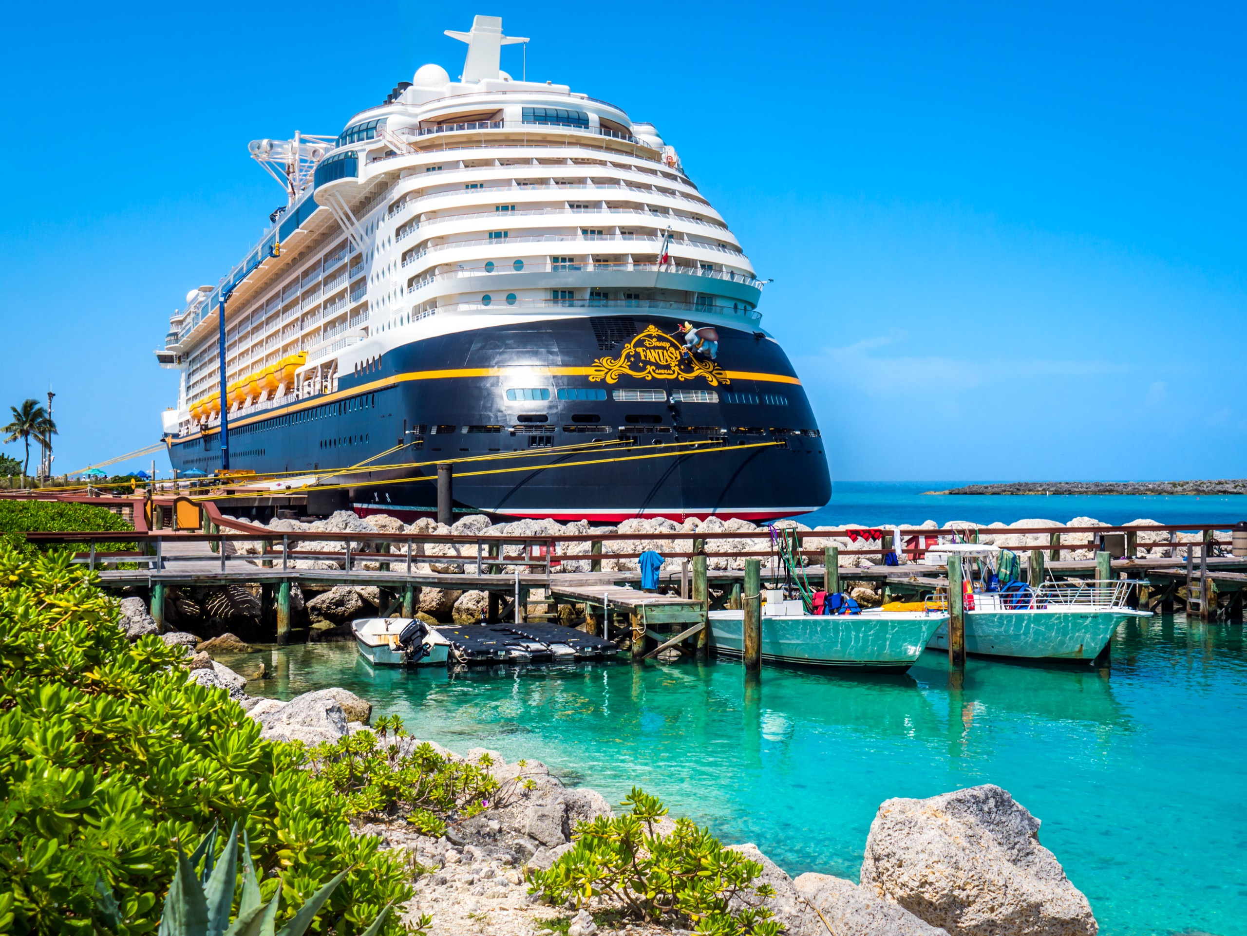 cruise lingo The Disney Fantasy luxury cruise ship sits docked at their private island, Castaway Cay. The water is blue and green and it's a clear day with blue a sky