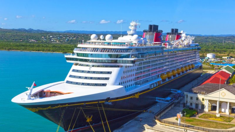 The Disney Fantasy luxury cruise ship is docked in Jamaica. The green foothills are in the distance on a mostly clear day.
