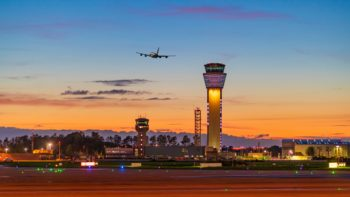 An airplane takes off at sunset over a runway at the Dublin airport. The lighted control tower dominates the scene.
