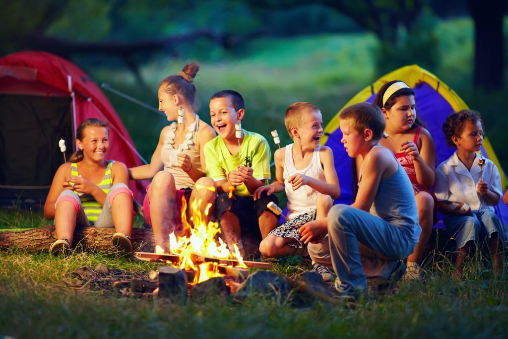A group of 7 friends sits near a campfire, holding marshmallows for roasting. They are laughing and smiling. There are two tents in the background for camping, one red and one yellow and blue.