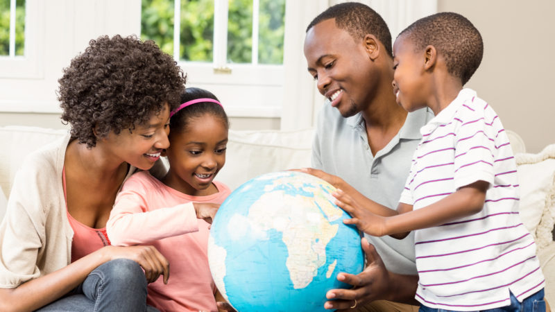Family looks at a globe