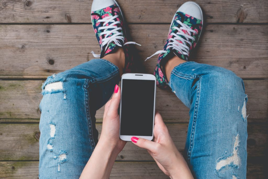 A sitting woman wearing stylishly ripped jeans holds a smartphone in both hands. She's wearing floral-print sneakers. You can only see her hands and legs in the picture.