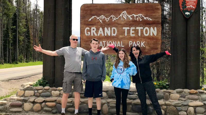 Family in front of National Park sign