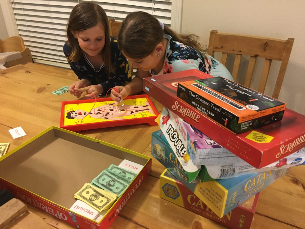 two girls playing operation with a stack of board games next to them