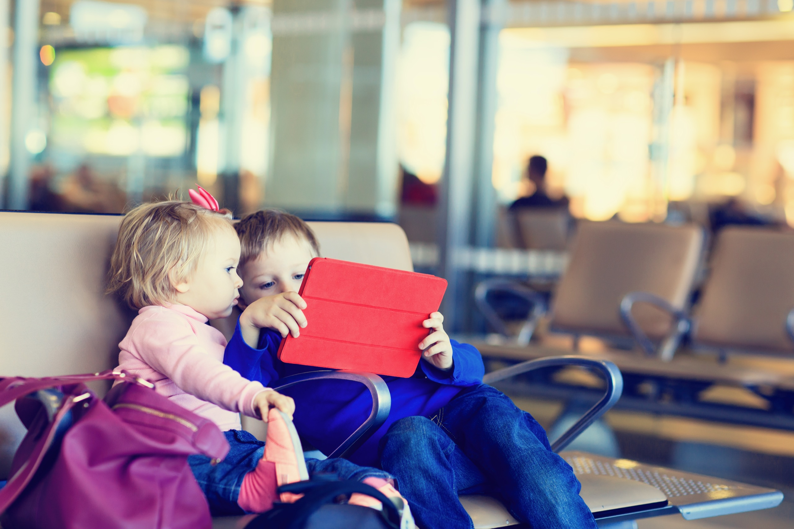 Two young children look at a digital tablet while sitting and waiting at an airport for their flight to board.